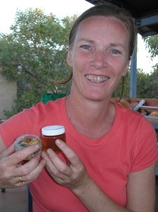 Robyn holding jars of acacia gum, raw on the left and dissolved in water on the right.